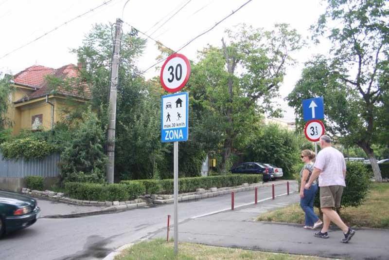 alei auto zona rezidentiala imagine cu semne rutiera si oameni pe trotuar zona cu restrictie de viteza 30 km pe ora